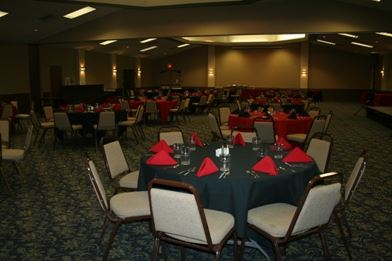 A round table with a black table cloth and red napkins on it and chairs all around the table